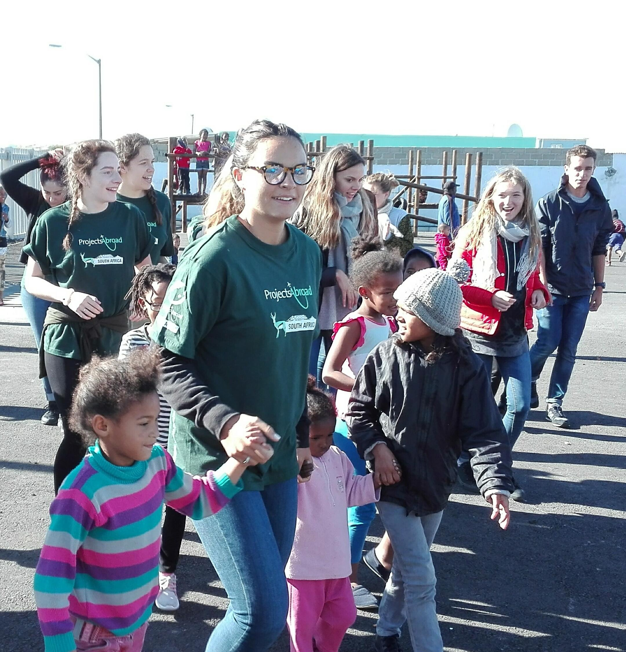 Female volunters with children in South Africa hold hands of local children and lead them on a walk at their Childcare Project.
